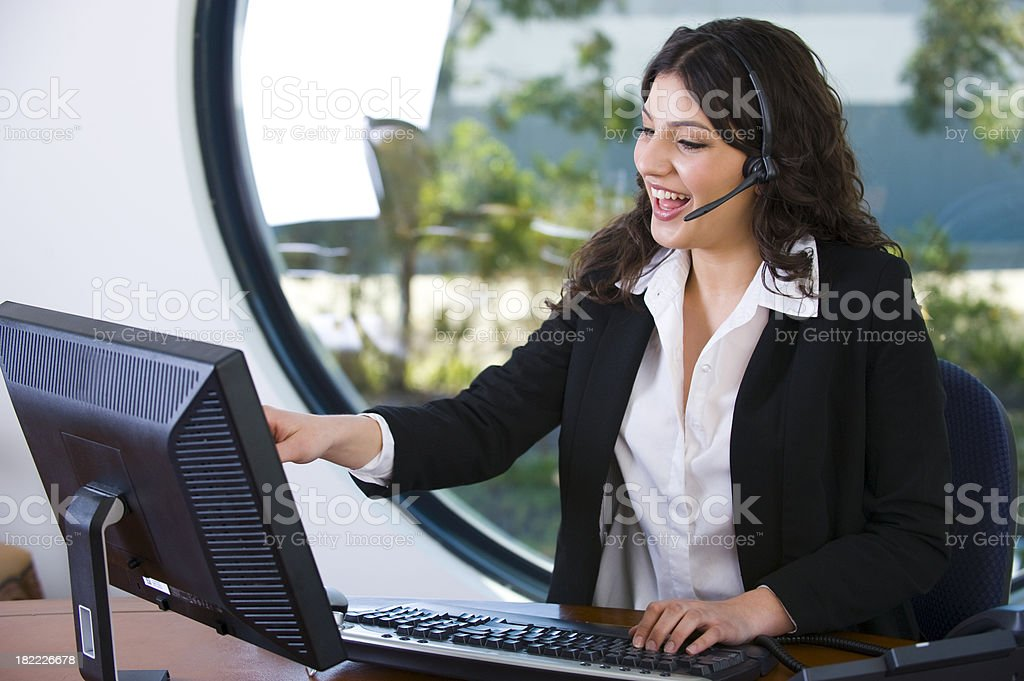 Attarctive woman talking with a headset and pointing stock photo