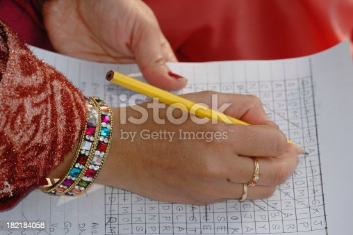 Young Indian lady doing a crossword puzzle.