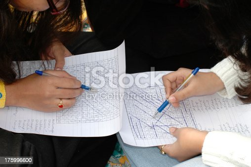 Young ladies doing a crossword puzzle.