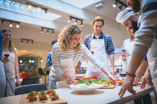 Die Teilnehmer des Kochkurses servieren ihre zubereiteten Speisen für Chefkoch – Foto
