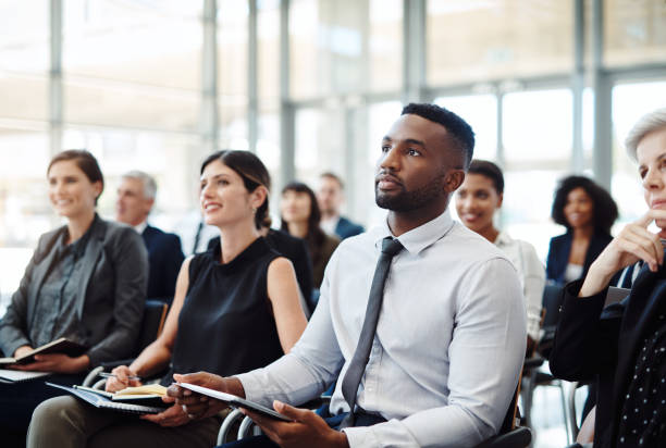 Attending a conference to develop their careers Shot of a group of businesspeople attending a conference attending stock pictures, royalty-free photos & images