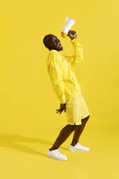 Attention! Black man shouting in megaphone on yellow background – zdjęcie