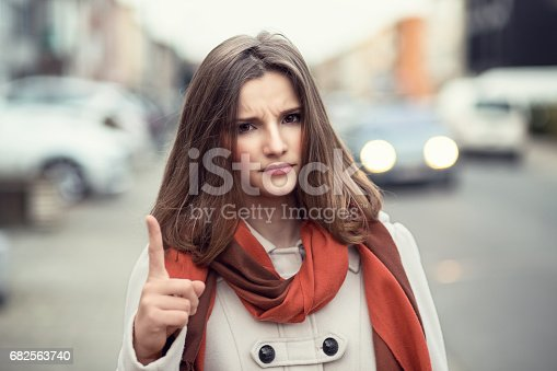 istock Attention! Closeup portrait headshot confident angry serious young girl business woman showing index finger for admonition isolated cityscape outdoor background. Multicultural mixt race asian russian 682563740