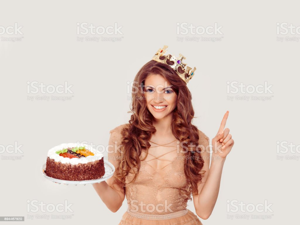 Attention guest. The happy middle age beautiful woman girl holds her birthday cake wearing party golden crown on white background wall showing pointing up with finger to copy space having idea smiling stock photo