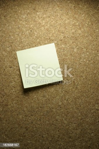Blank postit on cork board with spotlight on it.