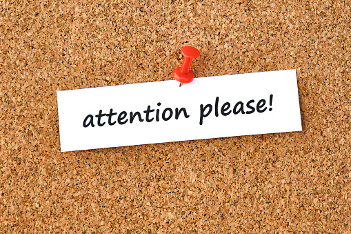 Attention please. Text written on a piece of paper or note, cork board background.