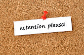 Attention please. Text written on a piece of paper, cork board background.