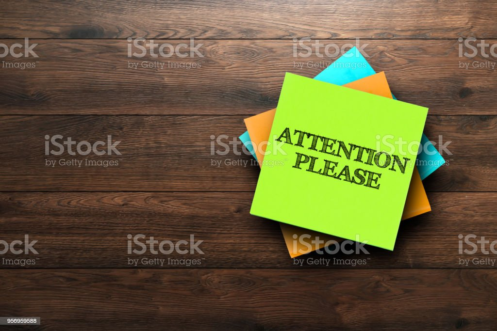Attention Please, the phrase is written on multi-colored stickers, on a brown wooden background. Business concept, strategy, plan, planning. stock photo