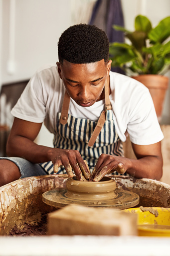 Shot of a young man working with clay in a pottery studio