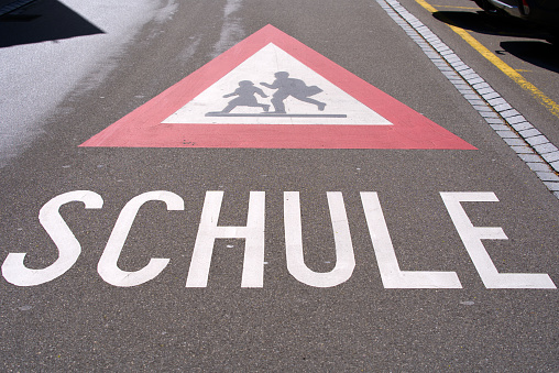 Attention traffic sign watch out for school kids with text Schule (German, translation is school) painted on road near school building.