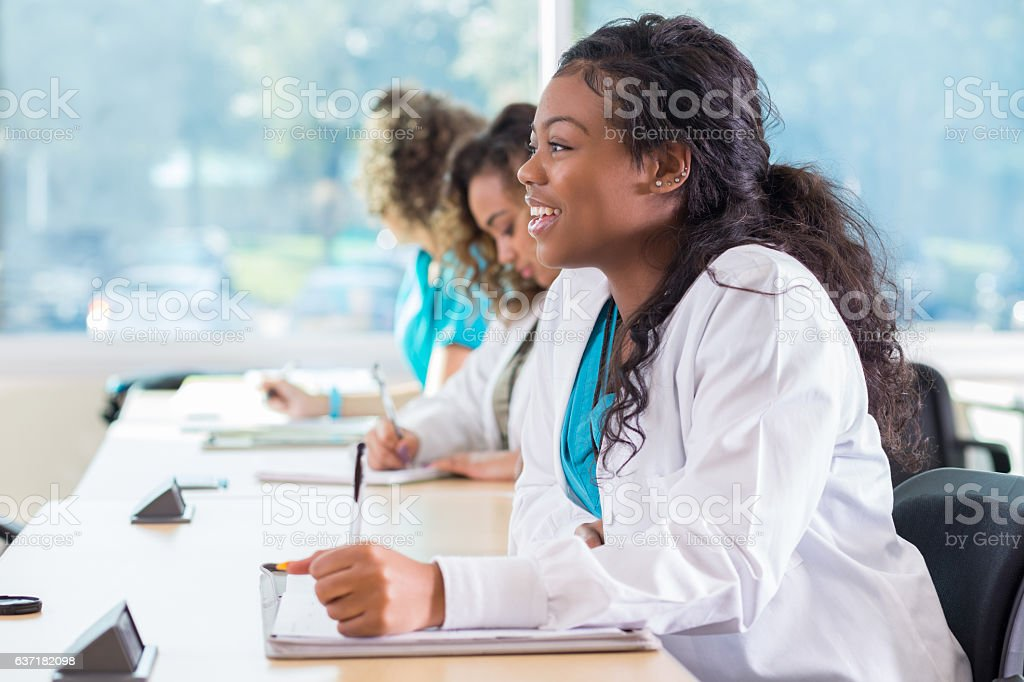 Attentive African American pre-med student takes notes in class stock photo