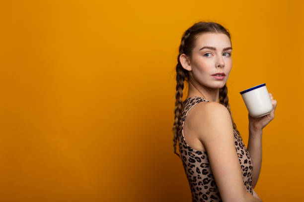 Attentive attractive blonde young woman against yellow background with copy space, dressed in crop top with tiger print. Drinks from a mug with coffee stock photo