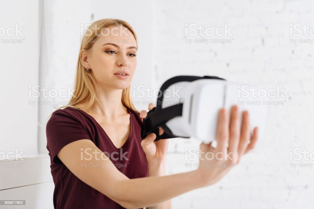 Attentive blonde looking at her mask stock photo