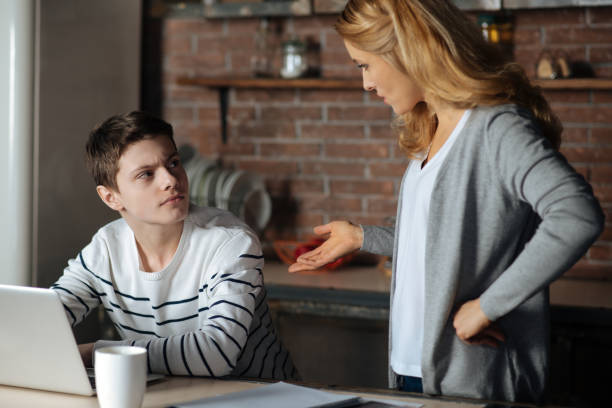 garçon attentif en regardant sa mère - parents photos et images de collection