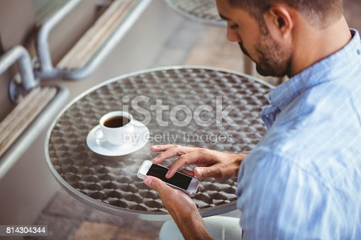 Attentive businessman sending text message outside the cafe