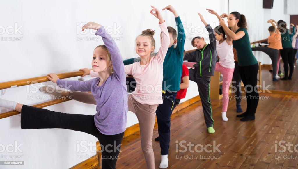 attentive children rehearsing ballet dance in studio - foto de acervo
