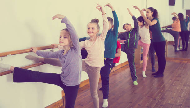 attentive children rehearsing ballet dance in studio - dance class stock photos and pictures