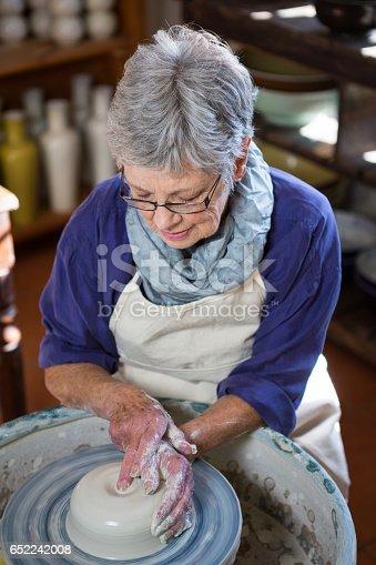 652188430 istock photo Attentive female potter making pot 652242008