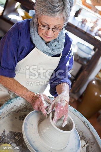652188430 istock photo Attentive female potter making pot 652242030