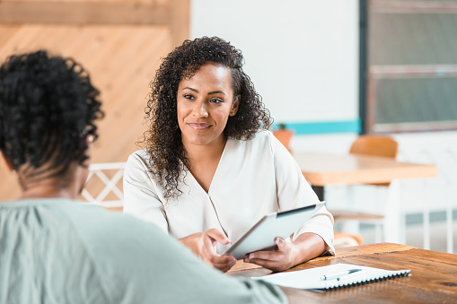 An attentive female financial advisor listens as a female client discusses financial strategy. The financial advisor is using a digital tablet.