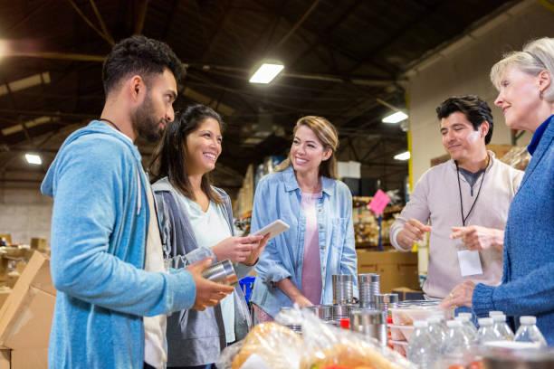 attentive food bank volunteers listen to food bank director - organizzazione no profit foto e immagini stock