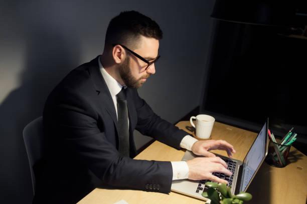 aufmerksamen mann arbeitet am projekt spät in die nacht. - achtsamkeit persönlichkeitseigenschaft stock-fotos und bilder