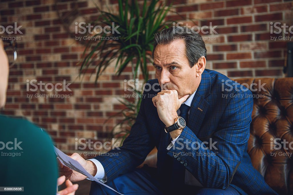 Attentive mature man in office of psychologist stock photo