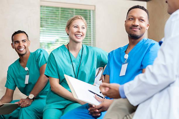 attentive medical staff talk with colleague - vêtements professionnels hospitaliers photos et images de collection
