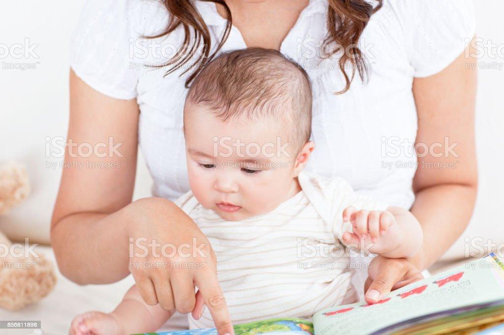 Aufmerksame Mutter zeigt Bilder in einem Buch zu ihrem süßen kleinen Sohn – Foto
