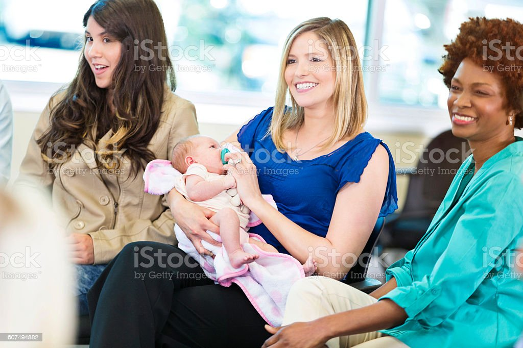 Attentive new mother participates in meeting stock photo