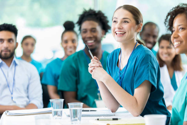 Attentive nursing students in class Cheerful Hispanic female nursing students smiles as she listens to a professor's lecture. nurses stock pictures, royalty-free photos & images