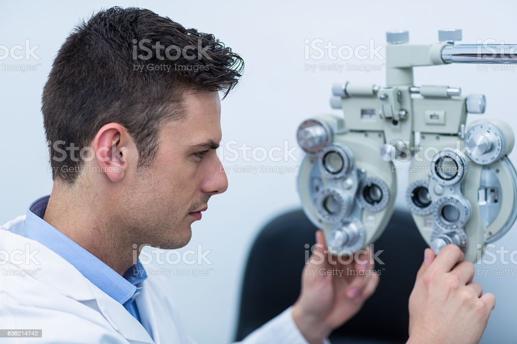 Attentive optometrist adjusting phoropter stock photo