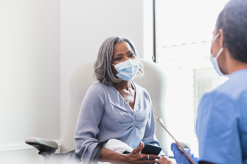 A senior woman holds attentively listens as a female doctor discusses her health. The patient is holding a smartphone. The patient and doctor are wearing protective face masks.
