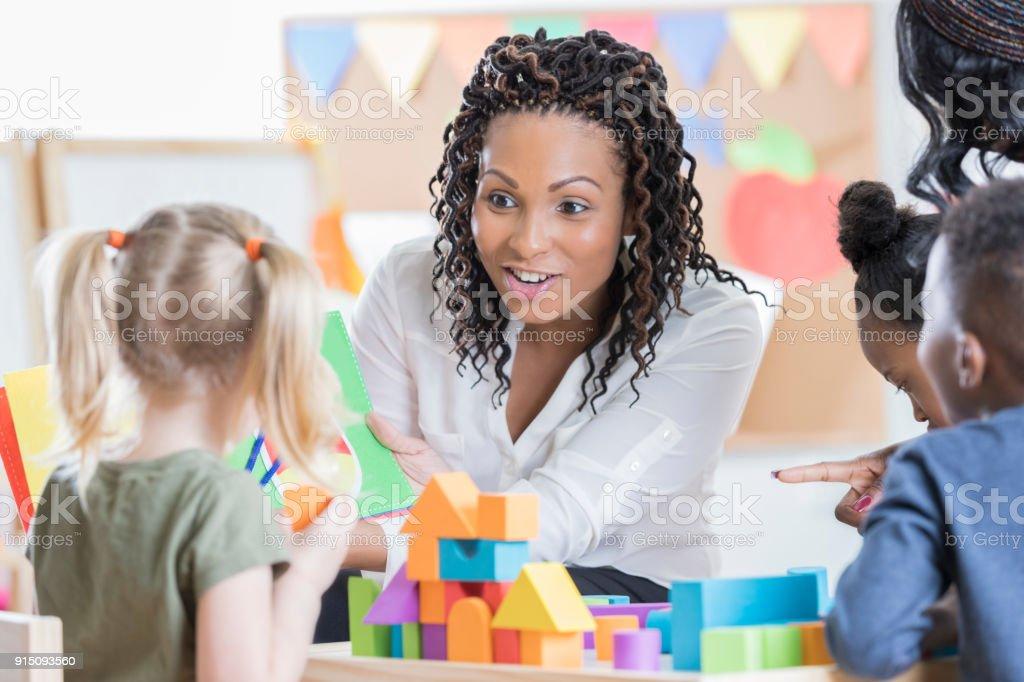 Attentive preschool teacher reads story book to school children stock photo