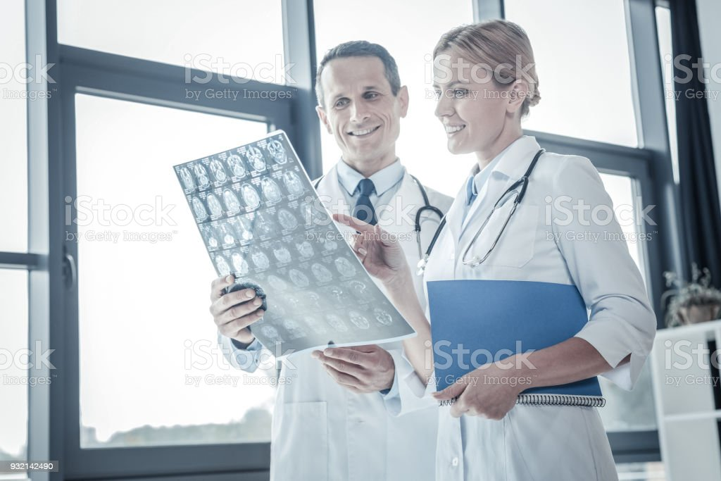 Attentive qualified doctors overlooking x-ray scan and smiling. stock photo
