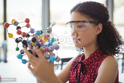 istock Attentive schoolgirl experimenting molecule model in laboratory 658909914