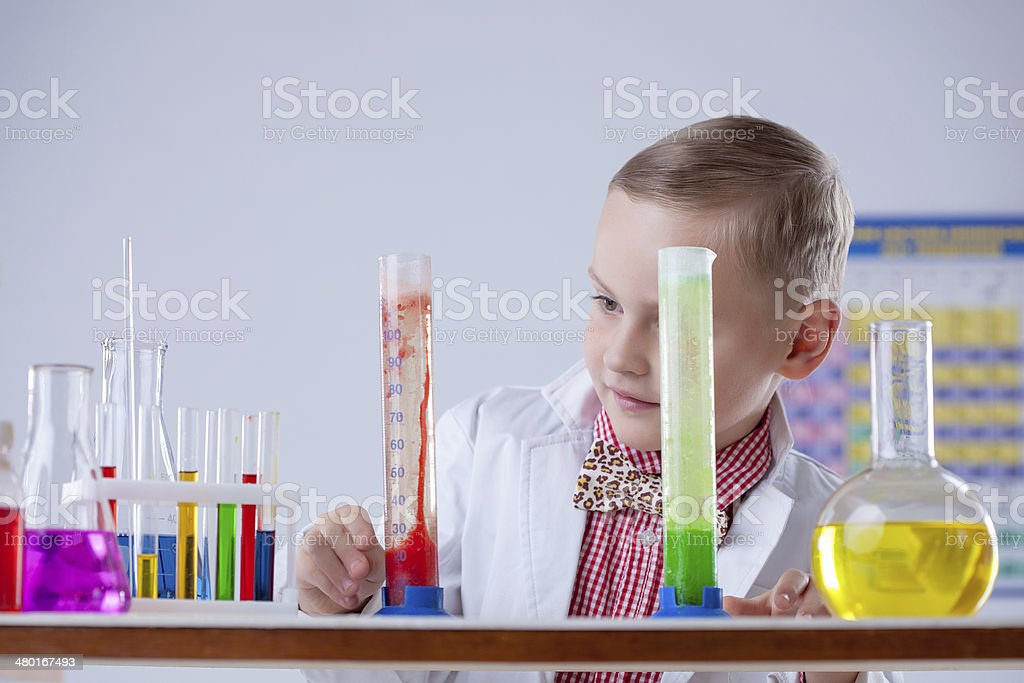 Attentive scientist watching chemical reaction stock photo