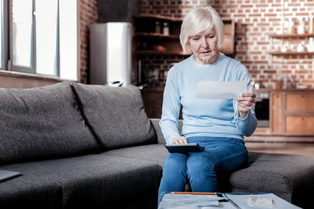 Attentive senior female calculating her savings Need to check. Serious pensioner bowing head while looking at counting social security stock pictures, royalty-free photos & images