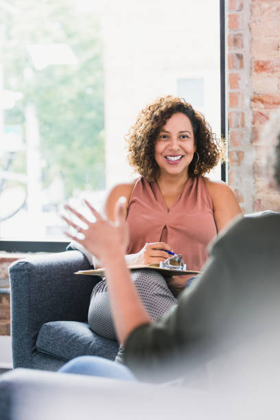 Attentive therapist listening to client stock photo