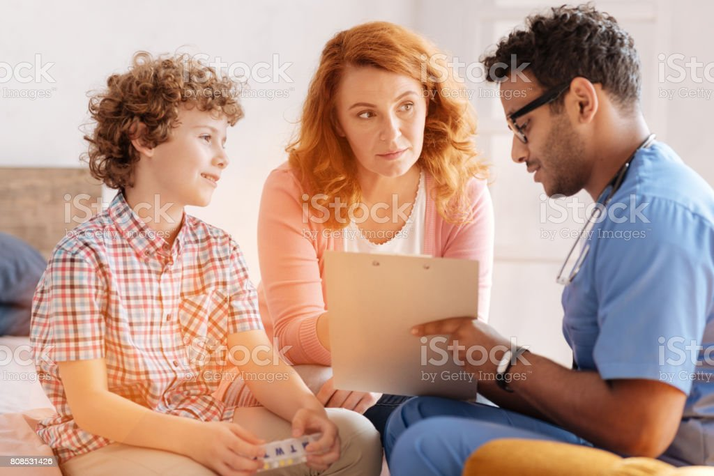 Attentive woman listening to the prescription of young doctor stock photo