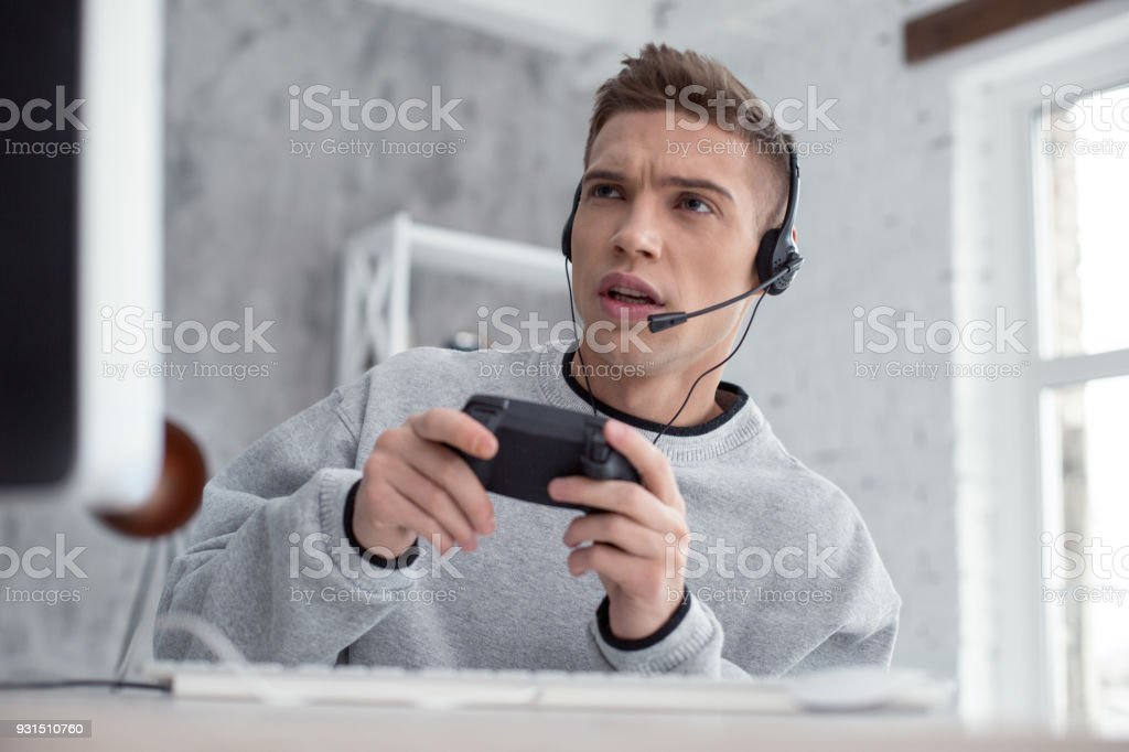 Attentive young man playing computer games stock photo