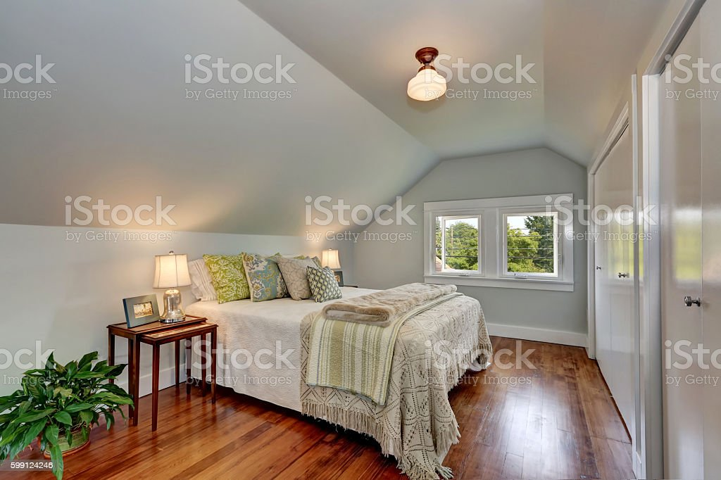 Attic bedroom interior with vaulted ceiling and hardwood floor. stock photo