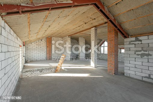 466705128istockphoto attic floor of the house. overhaul and reconstruction. Working process of warming inside part of roof. House or apartment is under construction, remodeling, renovation, restoration. 1076197480