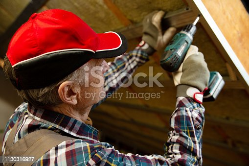 466705128 istock photo Attic insulation and renovation. Man fixing metal frame using an electric screwdriver on ceiling covered with rock wool 1130316927