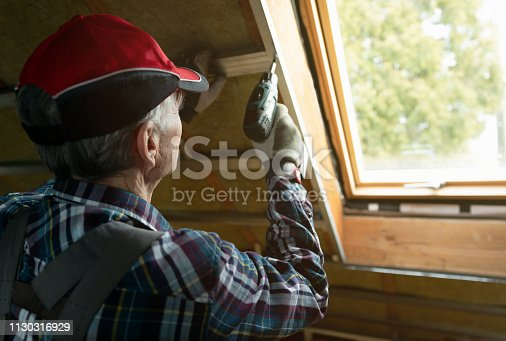 466705128 istock photo Attic insulation and renovation. Man fixing metal frame using an electric screwdriver on ceiling covered with rock wool 1130316929