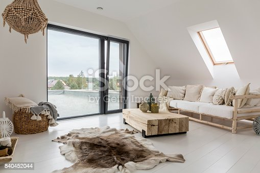 White attic room with balcony and wooden decorative accessories