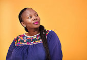 Shot of mature african woman looking away and thinking against yellow background