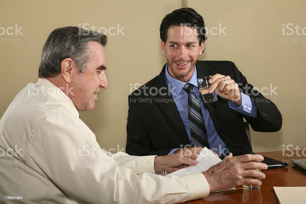 Attorney Drinking Water While Discussing Legal Documents with Client Attorney Drinking Water While Discussing Legal Documents with Client.See more from this series: 60-69 Years Stock Photo