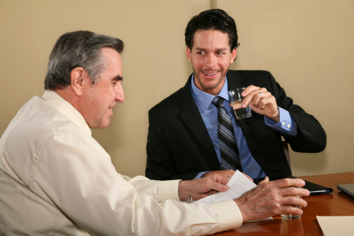 Attorney Drinking Water While Discussing Legal Documents With Client Stock Photo - Download Image Now