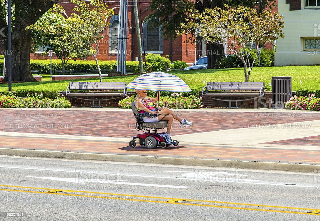attracive lady rides in her electric wheelchair with a parasol stock photo